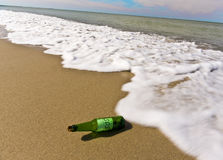 The bottle thrown out by the sea. Thrown out by a wave on sandy coast a bottle with note SOS Stock Photography