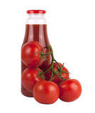 Bottle of tomato juice with tomatoes. Bottle of tomato juice with branch of tomatoes isolated on white background Royalty Free Stock Photography