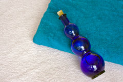 Bottle and towel. A colored folded towel and a  glass bottle Stock Images