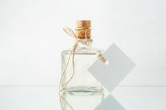 Bottle with transparent liquid and empty label on the light back Royalty Free Stock Photos