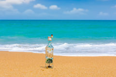 Bottle with tree  and butterfly inside on a beach Stock Photos