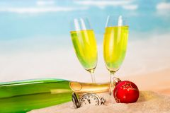 A bottle and two glasses with champagne, clock, Christmas ball i royalty free stock photos