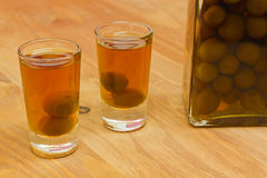 Bottle and two shots of homemade sloes liqueur Stock Image