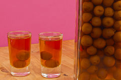 Bottle and two shots of homemade sloes liqueur Stock Images