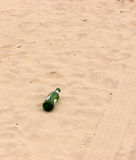 Bottle, tyre tracks in sand Stock Photos