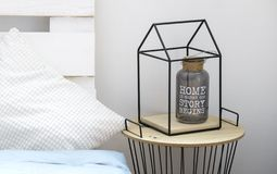 Bottle vase with quote about home inside metal house shape frame on table. Bottle vase with quote about home inside metal house shape frame on side table royalty free stock photo