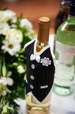 Bottle of vine in the costumes of groom Stock Photos