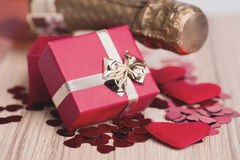 Bottle of vine, red hearts and small present Stock Image
