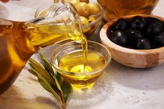 Bottle virgin olive oil and oil in a bowl with some olives.  Stock Images