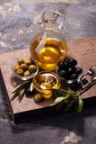 Bottle virgin olive oil and oil in a bowl with some olives.  Royalty Free Stock Photos