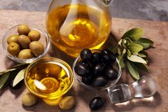 Bottle virgin olive oil and oil in a bowl with some olives.  Stock Photos