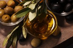Bottle virgin olive oil and oil in a bowl with some olives.  Royalty Free Stock Images