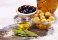 Bottle virgin olive oil and oil in a bowl with some olives.  Royalty Free Stock Image