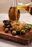 Bottle virgin olive oil and oil in a bowl with some olives.  Royalty Free Stock Photography