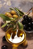 Bottle virgin olive oil and oil in a bowl with some olives.  Stock Image