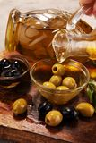 Bottle virgin olive oil and oil in a bowl with some olives.  Stock Photo