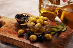 Bottle virgin olive oil and oil in a bowl with some olives.  Stock Photography