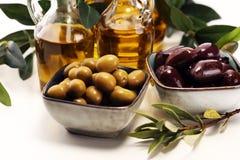 Olives. Bottle virgin olive oil and oil in a bowl with some oliv. Bottle virgin olive oil and oil in a bowl with some olives royalty free stock photo