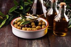 Olives. Bottle virgin olive oil and oil in a bowl with some oliv. Bottle virgin olive oil and oil in a bowl with some olives stock images
