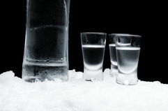 Bottle of vodka with glasses standing on ice on black background Royalty Free Stock Images