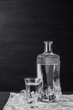 Bottle of vodka with glasses on the wooden table Royalty Free Stock Images