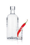 Bottle of vodka and shot glass with red chili pepper Stock Images