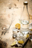 Bottle of vodka with shot glasses and lemon. Royalty Free Stock Photography