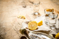 Bottle of vodka with shot glasses and lemon. Royalty Free Stock Images