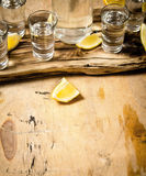 Bottle of vodka with shot glasses and lemon. Stock Photos