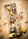 Bottle of vodka with shot glasses and lemon. Royalty Free Stock Photo