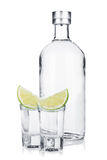 Bottle of vodka and shot glasses with lime slice Stock Photography