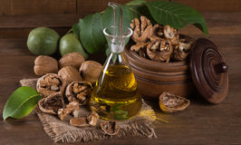Bottle of walnut oil and nuts with leaves Royalty Free Stock Images