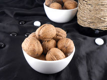 Bottle and walnuts on black material with stones Royalty Free Stock Photos
