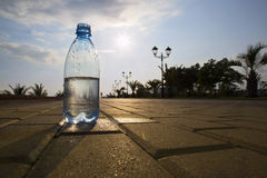 Bottle of water costs on the backdrop of the waterfront. The water bottle is at sunset Royalty Free Stock Photography