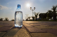 Bottle of water costs on the backdrop of the waterfront. The water bottle is at sunset Stock Photo