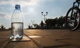 Bottle of water costs on the backdrop of the waterfront. The water bottle is at sunset Stock Photography