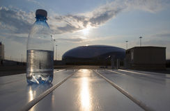 Bottle of water costs on the background of the Olympic village in Sochi. The water bottle is at sunset Stock Photo