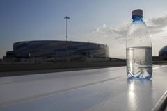 Bottle of water costs on the background of the Olympic village in Sochi. The water bottle is at sunset Royalty Free Stock Photo