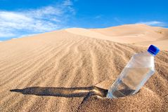 Bottle of water in desert. Plastic bottle of water on sand dune in desert with blue sky and cloudscape background Stock Photo