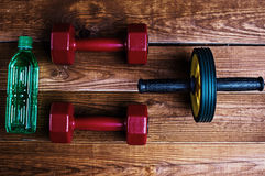 Bottle of water and dumbbells Royalty Free Stock Images