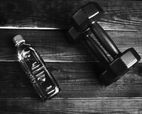 A bottle of water and dumbbells Royalty Free Stock Image