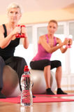 Bottle of water in front of group doing fitness Royalty Free Stock Photography
