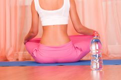 Bottle of water in front of sporty woman Stock Image