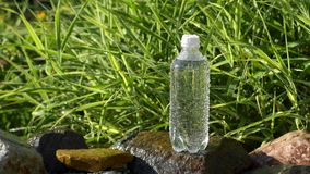 Bottle of water in garden. With water drops stock video