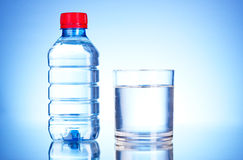Bottle of water and glass on blue Stock Photography