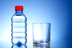 Bottle of water and glass on blue Royalty Free Stock Photos