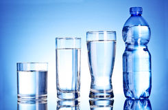 Bottle of water and glass on blue Stock Images