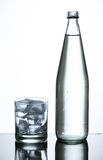 Bottle of water and glass of ice Royalty Free Stock Image