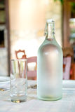 Bottle of water and a glass on a table in a restaurant Stock Images
