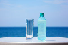 Bottle of water and glass on table under open sky Stock Photo